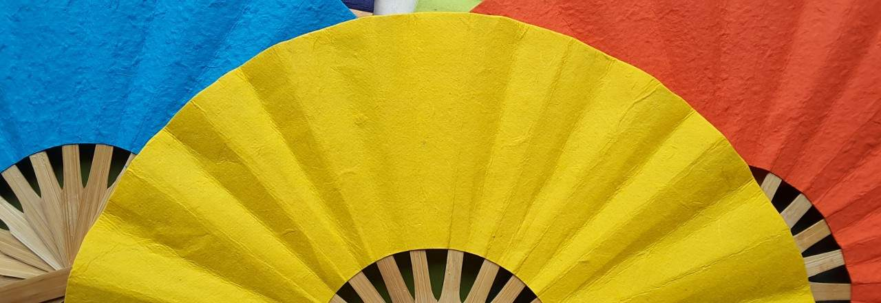 Three paper wedding fans in solid yellow, blue, red
