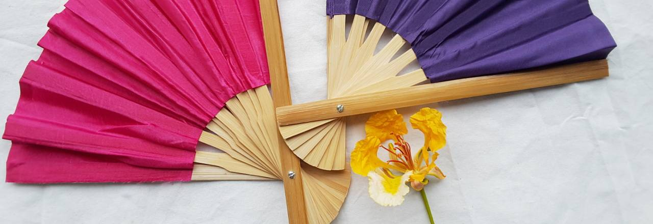 Two, half open, solid color silky fabric wedding fans in pink and violet